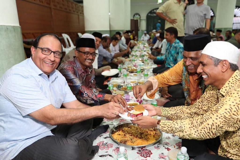 ERATKAN JALINAN: Menteri Perhubungan dan Penerangan, Encik S. Iswaran (kiri ) dan pengerusi Masjid Jamae Chulia, Encik Shaick Fakrudeen S Ali (di kirinya), mengambil kurma yang dihulurkan pegawai masjid dalam majlis berbuka puasa yang turut disertai seramai 1,400 jemaah di masjid itu Sabtu lalu. – Foto FACEBOOK S. ISWARAN