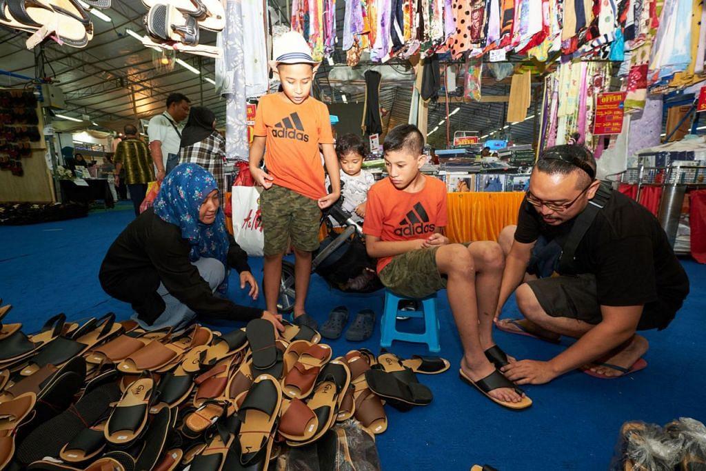 BAZAR GEYLANG SERAI: CARI CAPAL: Encik Muhammad Faizal Mohammad Fadzillah (kanan), isterinya, Cik Diyana Mohamed Yusoff (kiri), sedang memilih capal untuk dibeli buat anak-anak lelaki mereka, Muhammad Amir Rusyaidi Muhammad Faizal (dua dari kanan), dan Muhammad Amir Irsyad Muhammad Faizal (dua dari kiri). Anak perempuan mereka, Nur Amira Auliya Muhammad Faizal, turut bersama. - Foto BH oleh ROSLEE ABDUL RAZAK