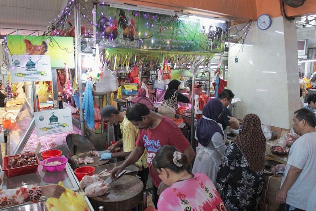 PASAR CHONG PANG: MERIAH DIRASAKAN: Kedai ayam di Pasar Chong Pang, Yishun, turut menghiasi kedai mereka dengan lampu lap-lip, menghidupkan suasana raya sambil pelanggan membeli bahan basah bagi juadah Raya. - Foto BH oleh IQBAL FAIZAL
