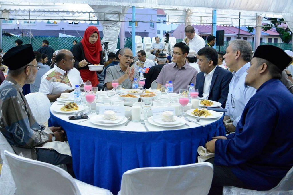 BUKA BERSAMA: Encik Masagos (tengah) menyertai satu majlis berbuka puasa anjuran Darul Arqam kelmarin, di mana badan itu telah menyampaikan cek $20,000 kepada Mercy Relief dan melancarkan buku panduan baru bagi muallaf. Bersamanya ialah antara lain Presiden Darul Arqam, Encik Imran Kuna (dua dari kiri) dan CEO Muis, Encik Esa Masood (empat dari kanan). - Foto DARUL ARQAM