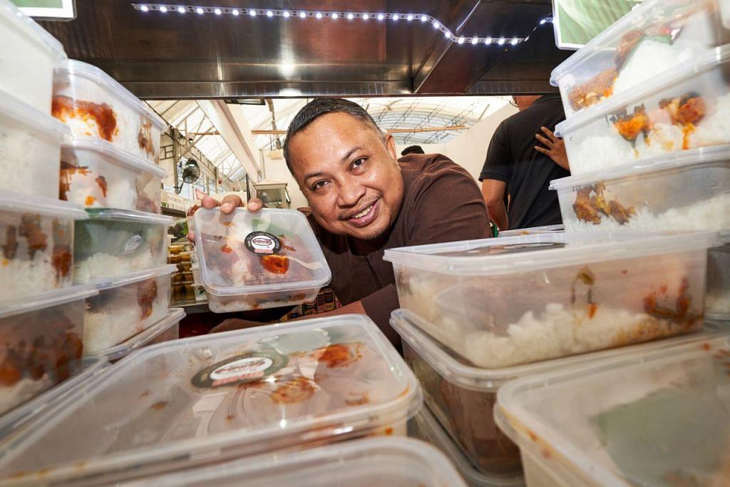 'NASI LEMAK POWER': Encik Badrol Hisam dengan bungkusan nasi lemak di gerainya yang terletak di Bazar Raya Utara. - Foto BH oleh ROSLEE ABDUL RAZAK