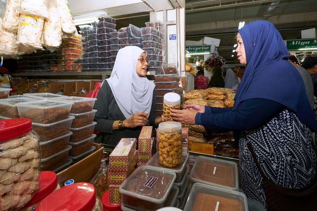 PASAR GEYLANG SERAI: CARI KUIH: Cik Norizah Sanan (kiri), 50-an tahun, sedang menjual sebotol kuih tart kepada seorang pelanggan di pasar Geylang Serai. - Foto BH oleh ROSLEE ABDUL RAZAK