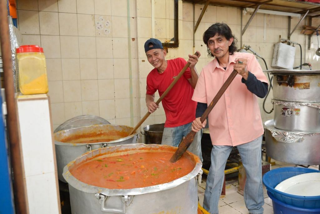 BERIANI 'POWER': Encik Syed Hafeez (kanan) bersama pekerjanya yang sedang menyediakan lauk dalca yang akan diberi bersama Nasi Beriani Dum semasa penghantaran ke rumah. - Foto BH oleh SHINTARO TAY