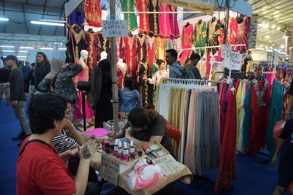 RIUH-RENDAH: Keadaan riuh-rendah di Bazar Geylang Serai hanya akan reda pada dinihari nanti, beberapa jam sebelum Muslim di Singapura pergi ke masjid untuk solat Hari Raya.
