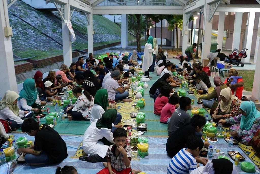 SEMANGAT KEMASYARAKATAN: Penduduk Jalan Kukoh berbuka puasa bersama. Para penerima bantuan juga menerima habuan makanan dan alat sekolah. – Foto PPIS