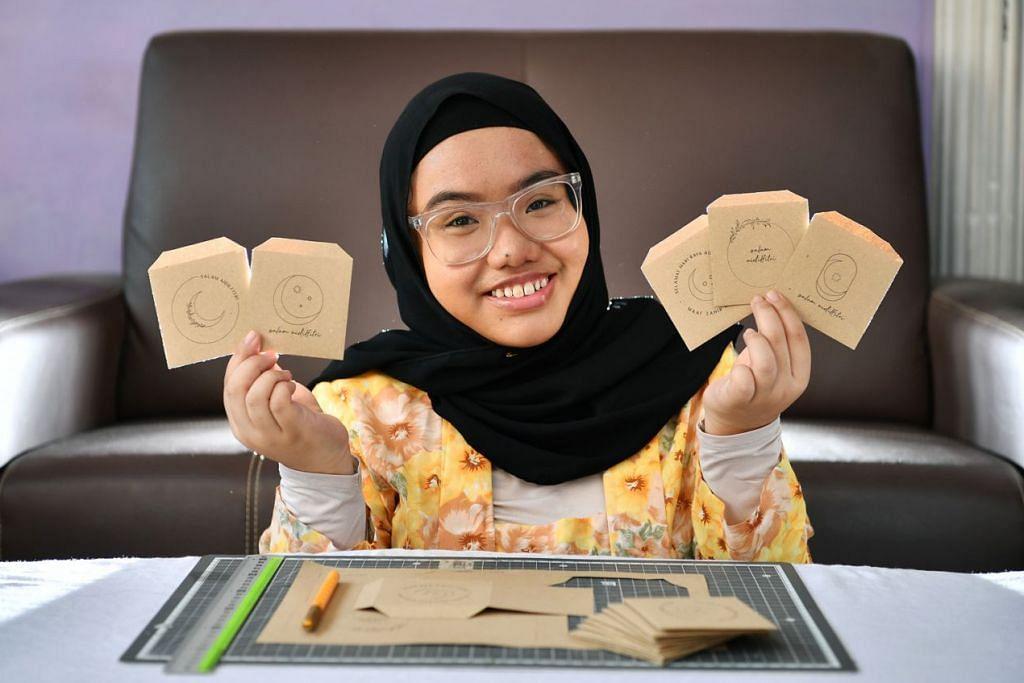 SAMPUL 'HIJAU': Cik Yulianna menghasilkan sampul duit Raya menggunakan kertas yang dikitar semula bagi mengurangkan pembaziran. - Foto BH oleh LIM YAOHUI