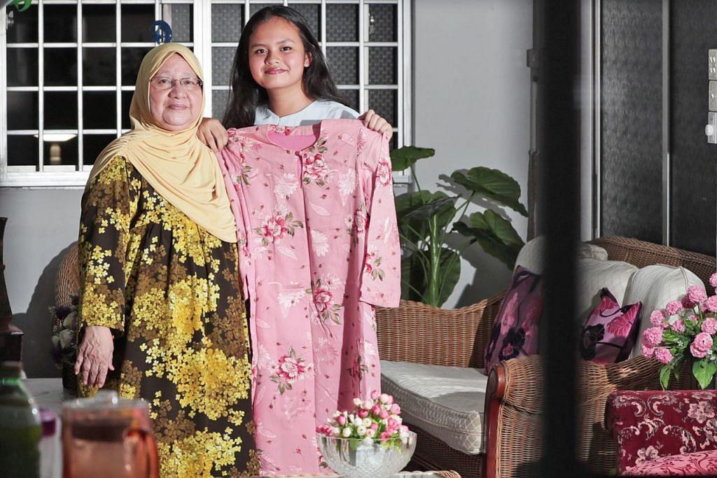 WARISAN TRADISI: Cik Rosilah Abdol Hamid mengimbas semula kenangan pakaian Raya dahulu dengan menunjukkan baju Raya lamanya kepada cucunya, Liyana Amirul Haque, sambil berharap anak cucunya akan meneruskan tradisi Raya seperti mengenakan baju Melayu. - Foto BM oleh KELVIN CHNG