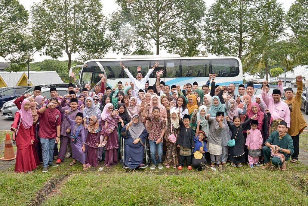 JALAN BERKELUARGA: Sebahagian daripada sekitar 90 anggota keluarga yang mengadakan lawatan ke rumah saudara-mara sempena Hari Raya, meluangkan masa bergambar di salah satu tempat perhentian, sebelum menyambung kunjungan mereka. - Foto BM oleh SHINTARO TAY