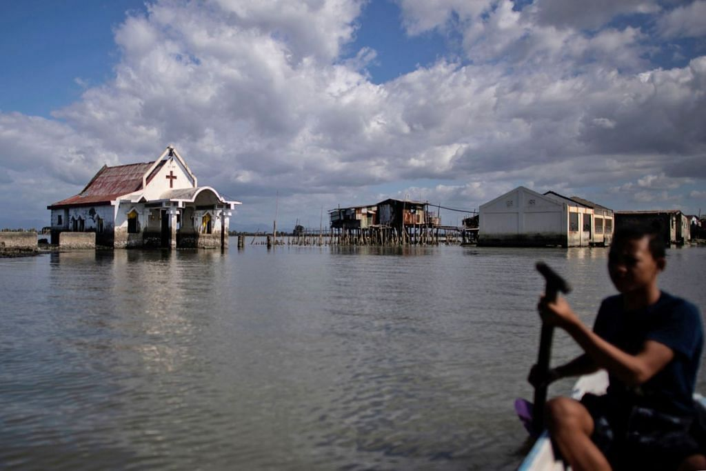 MENDAP HINGGA DIANCAM TENGGELAM: Dulu penduduk Sitio Pariahan berjalan kaki ke gereja setempat. Sekarang, mereka terpaksa berenang atau menaiki bot kerana kawasan di wilayah Bulacan di Utara Manila itu mengalami pemendapan hingga ditenggelami air yang mengalir dari Teluk Manila. - Foto AFP