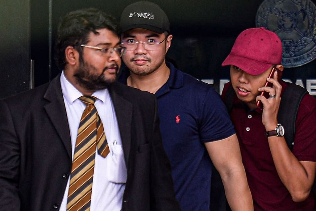 DAKWA MENTERI: Encik Haziq Aziz (tengah) dirakam meninggalkan balai polis Dang Wangi di Kuala Lumpur Sabtu lalu. - Foto EPA-EFE