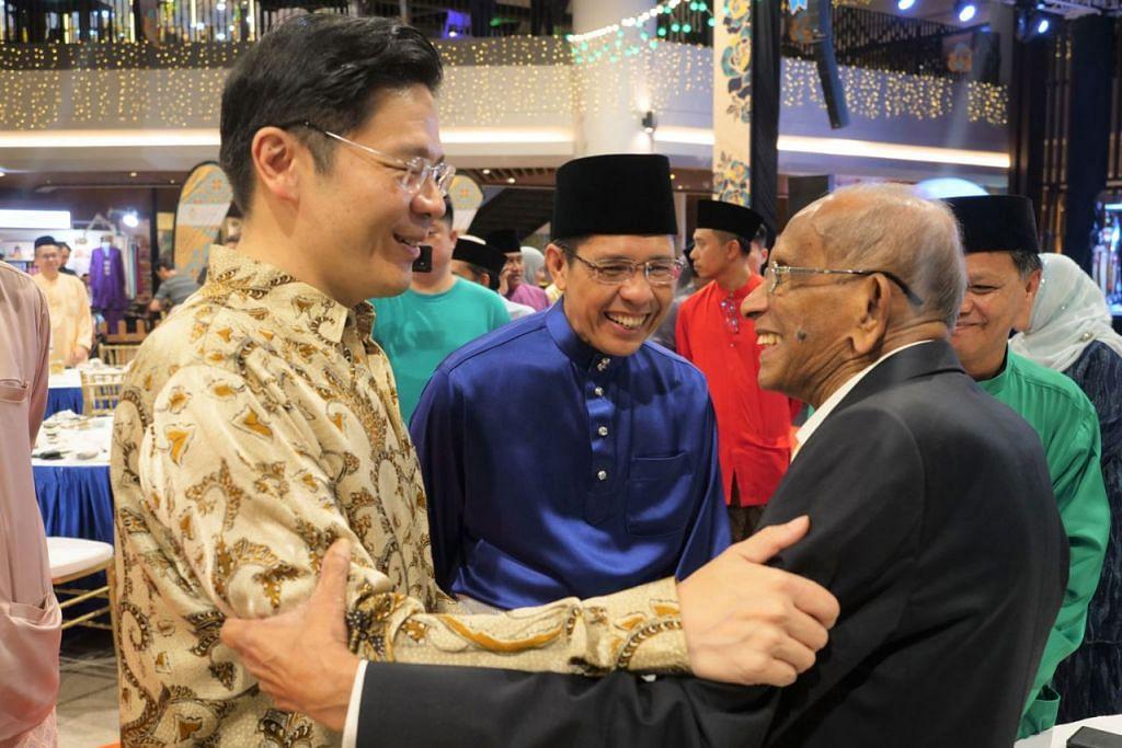 BERAYA DI WGS: Encik Lawrence Wong (kiri) dan Dr Mohamad Maliki Osman (dua dari kiri) beramah mesra dengan tetamu majlis Perjumpaan Hari Raya WGS baru-baru ini termasuk Pengerusi Persatuan Karyawan Muzik Singapura, Yusnor Ef (kanan). - Foto WGS