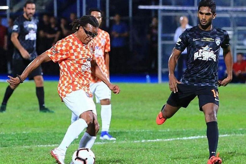 Pemain midfield pasukan Singa, Hariss Harun (kanan) mengejar lagenda bola sepak Belanda, Edgar Davids dalam satu perlawanan amal 'all-star' di Stadium Larkin, Johor, Ahad lalu. FOTO: JDT
