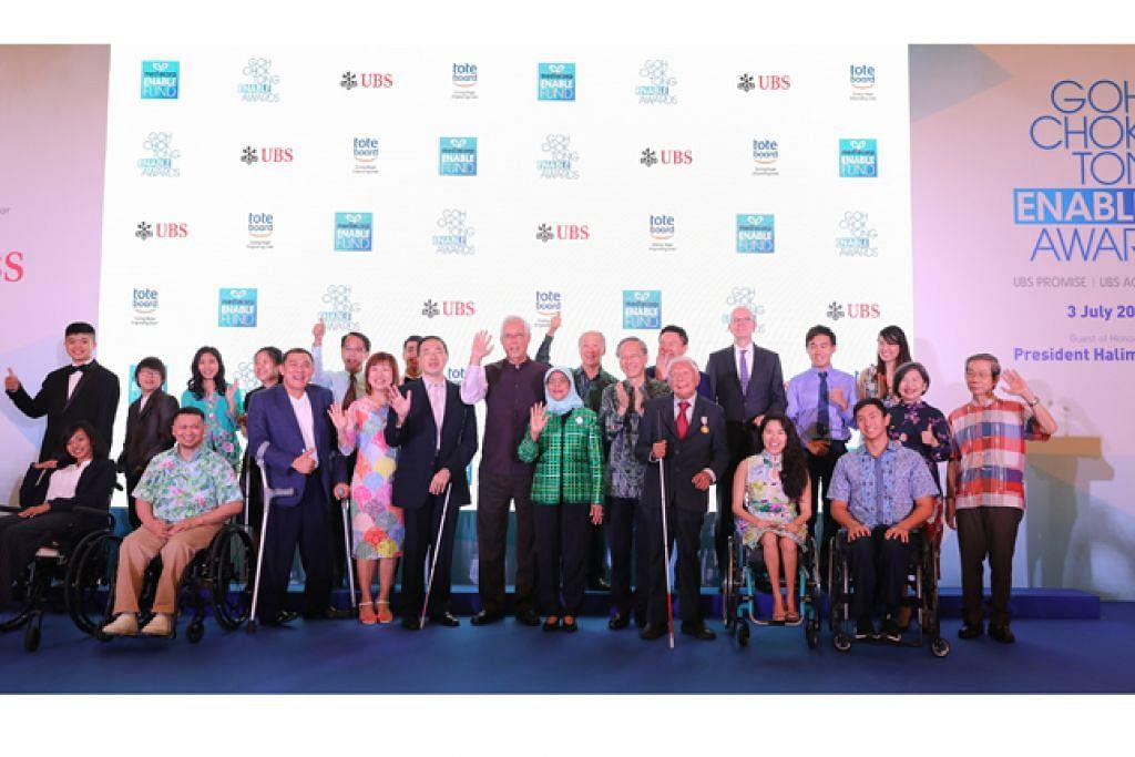 DIIKTIRAF: Presiden Halimah (berbaju hijau) dan Menteri Kanan Emeritus (ESM) Goh Chok Tong (sebelahnya) bersama 13 individu kurang upaya yang diiktiraf dengan Anugerah Enable Goh Chok Tong atas pencapaian luar biasa mereka dan potensi mereka dalam bidang masing-masing. - Foto BH oleh ONG WEE JIN
