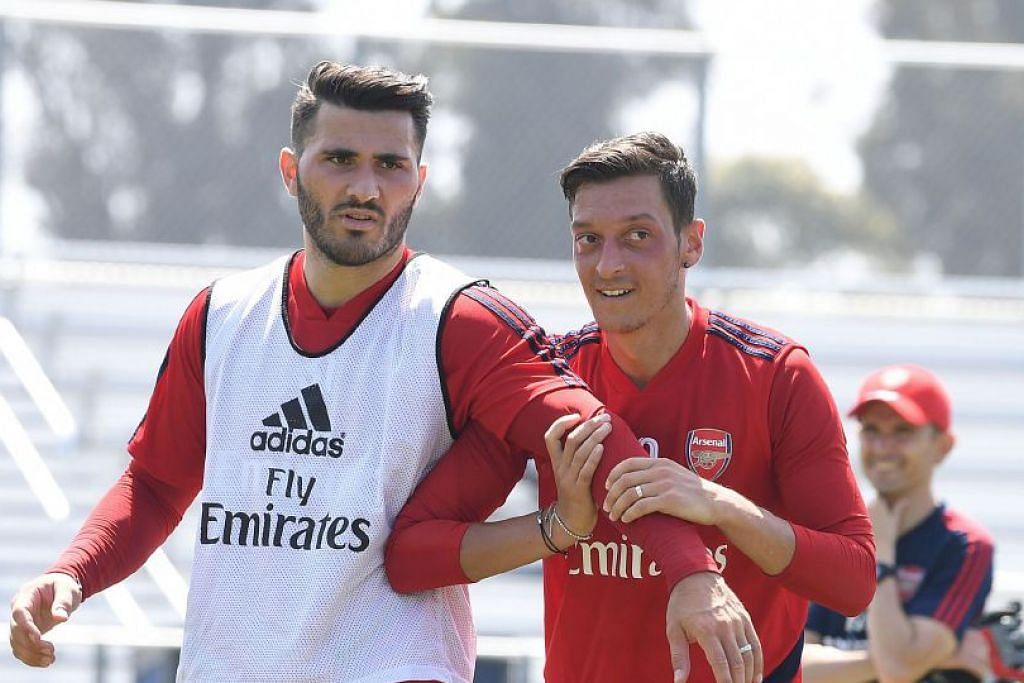 Pemain Arsenal Sead Kolasinac (kiri) dan Mesut Ozil bertarung dengan perompak yang memberhentikan kereta mereka di London.