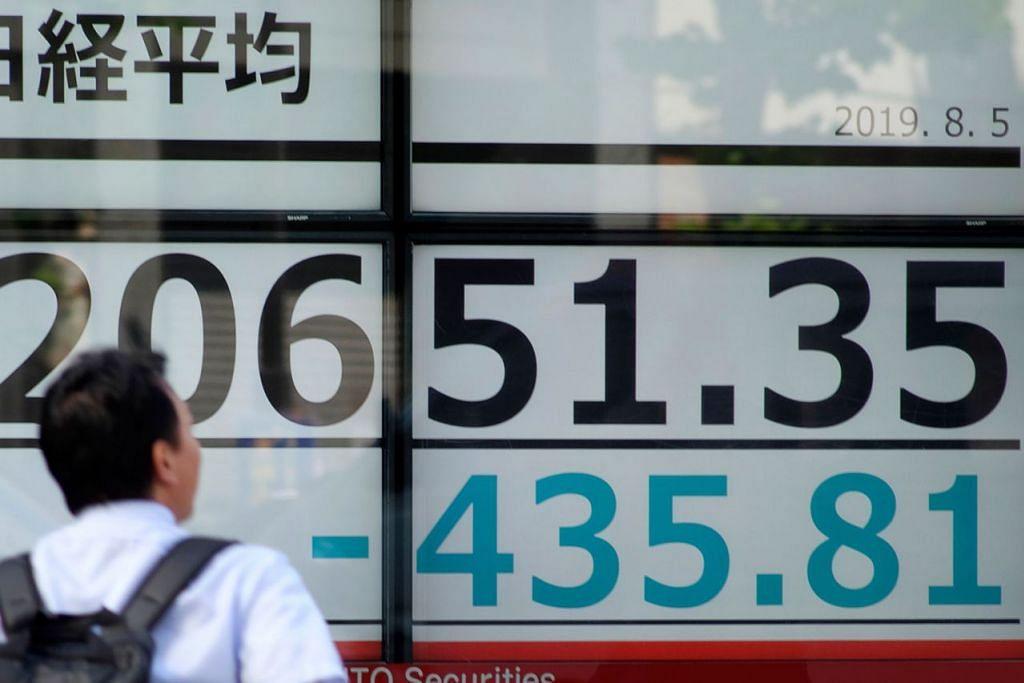 KEMEROSOTAN BESAR: Seorang lelaki melihat papan tanda elektronik yang menunjukkan harga saham di bursa Tokyo yang merosot. - Foto AFP
