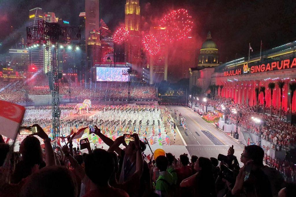 DIRGAHAYU SINGAPURA: Para penonton dan peserta menikmati pertunjukan bunga api yang menyemarakkan langit malam di sekitar kawasan Padang semalam sambil memetik gambar. Bunga api kembang mekar setelah ikrar negara dilafaz dan lagu kebangsaan dinyanyikan. – Foto BH oleh KUA CHEE SIONG