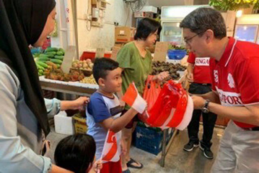 DI NEE SOON CENTRAL: BENDERA BUAT SI CILIK: Profesor Madya Faishal Ibrahim mendekati penduduk cilik di sebuah pasar daerah Nee Soon Central. – Foto FACEBOOK PROFESOR MADYA FAISHAL IBRAHIM