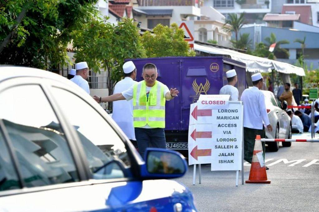Relawan dari Shinnyo-en membantu menguruskan trafik semasa solat Aidilfitri di Masjid Abdul Razak pada 11 Ogos.