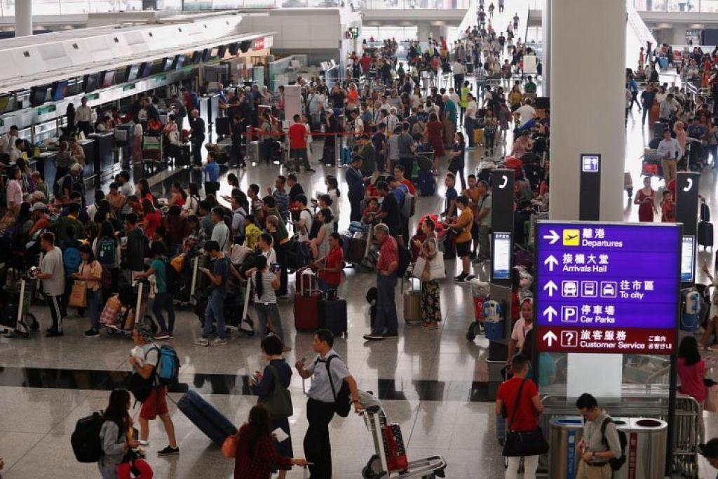 OPERASI DISAMBUNG SEMULA: Pengembara beratur untuk check-in di Lapangan Terbang Hong Kong setelah ia dibuka semula setelah penerbangan dibatalkan akibat bantahan di lapangan terbang itu semalam. -Foto REUTERS.