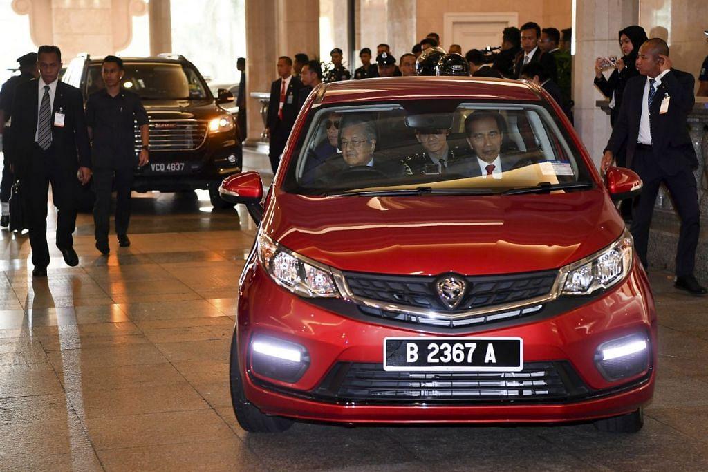 MEMANDU KERETA UNTUK PELAWAT NEGARA: Perdana Menteri Tun Dr Mahathir Mohamad memandu Kereta Proton Persona untuk membawa Presiden Indonesia Joko Widodo ke jamuan tengahari (9 Ogos). -Foto: ST.