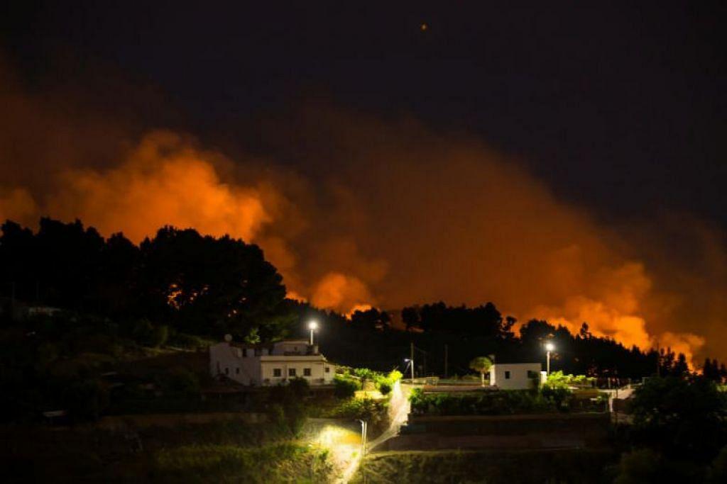 KEBAKARAN TANAH GERSANG: Api dan asap tebal akibat kebakaran hutan boleh dilihat dari perkampungan Valleseco di Gran CanariA di Kepulauan Canary, Sepanyol. -Foto REUTERS.