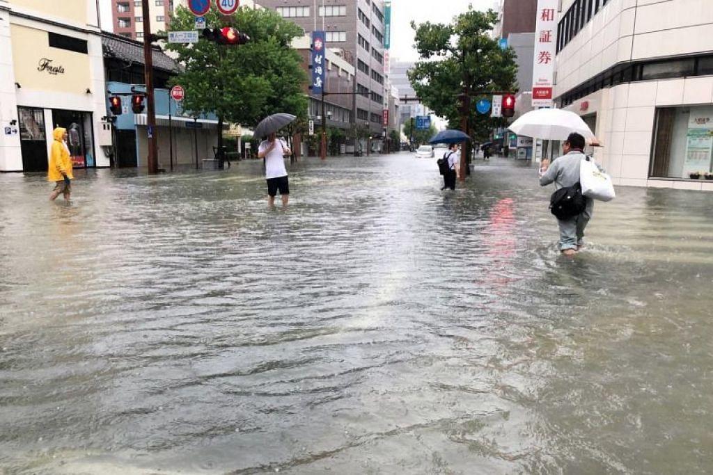 AIR NAIK KE LUTUT: Orang awam meredah banjir setinggi lutut di jalan raya berdekatan stesen kereta api Saga, di wilayah Saga, pada 28 Ogos 2019. -Foto REUTERS.
