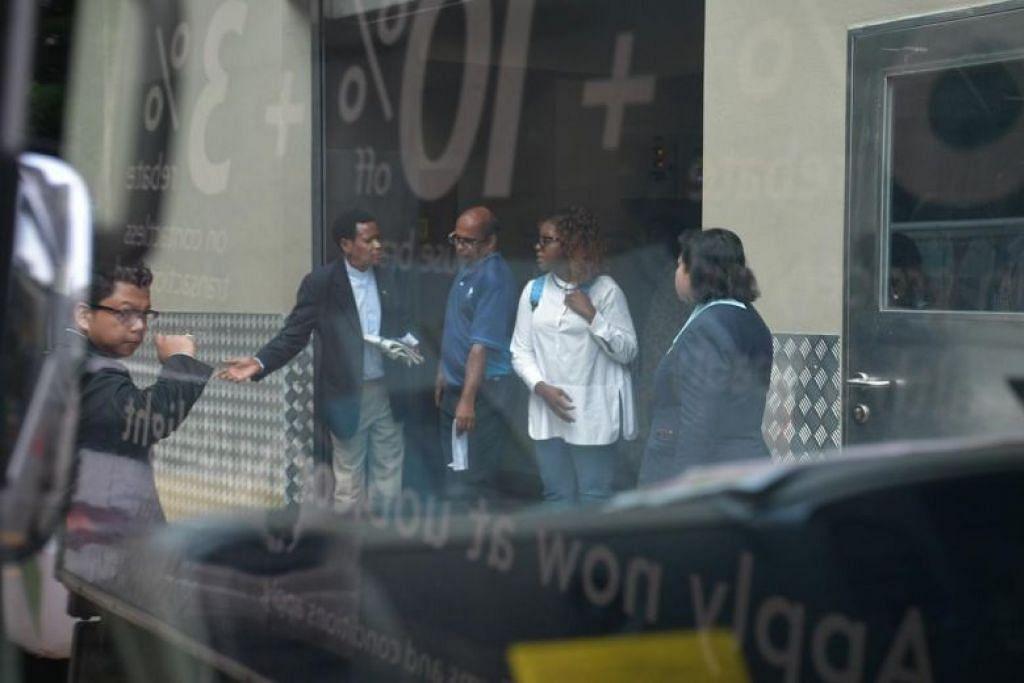 Seorang lelaki berpakaian sut gelap dengan bendera Zimbabwe, bersama beberapa orang lain, dilihat di sebelah van Singapore Casket berhampiran rumah mayat Hospital Gleneagles. -Foto: ST/KUA CHEE SIONG