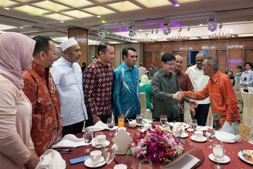 HARGAI SUMBANGAN RELAWAN: Encik Heng (empat dari kanan) beramah mesra dengan para tetamu yang turut disaksikan Menteri Ehwal Dalam Negeri merangkap Undang-Undang K. Shanmugam (dua dari kanan). – Foto BM oleh ALPHONSUS CHERN