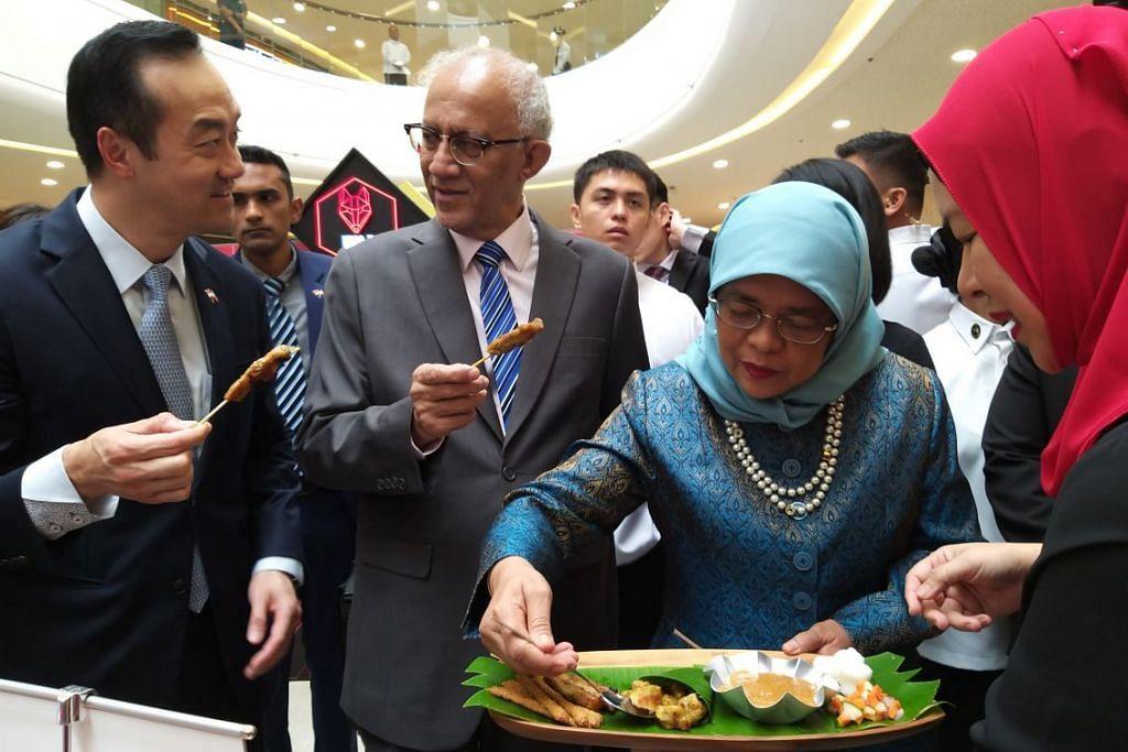 CUBA SATE: Presiden Halimah Yacob dan suami, Encik Mohamed Abdullah Alhabshee, mencuba sate Jumain Sataysfaction di acara makanan dan gaya hidup Singaporium di pusat beli-belah The Podium di Manila. Foto IRMA KAMARUDIN
