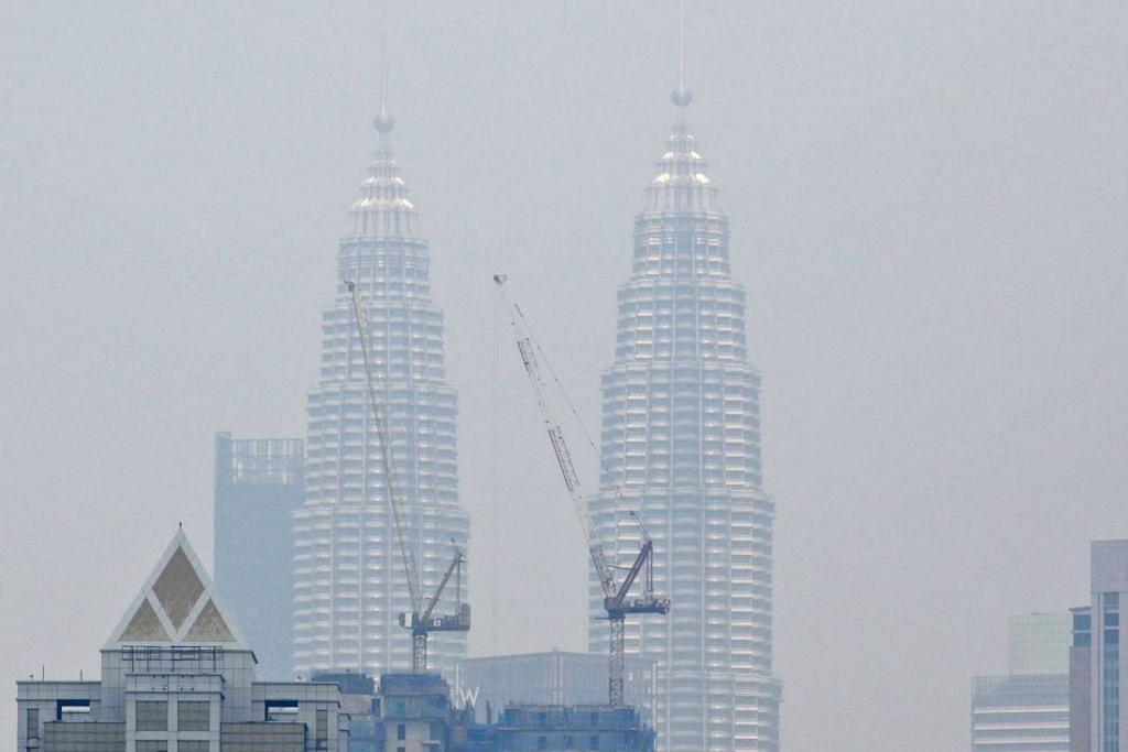 UDARA TIDAK SIHAT: Menara Kembar Petronas di Kuala Lumpur semalam kelihatan diselubungi jerebu tebal. - Foto AFP