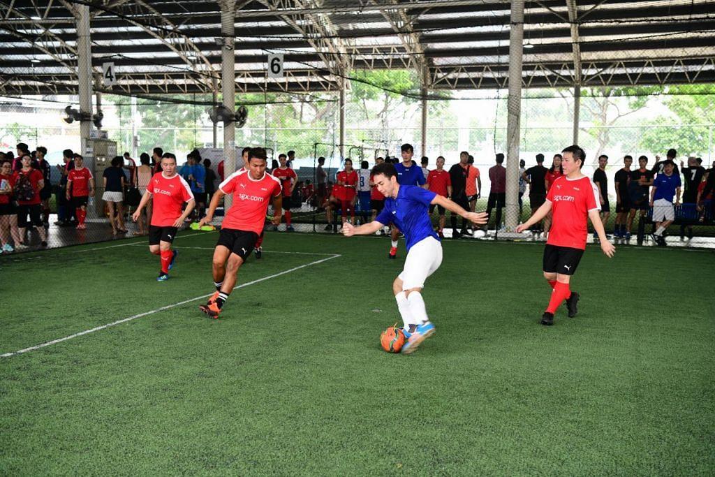 FUTSAL AMAL: Pasukan Pengurusan SGX (jersi merah) menentang pasukan artis Mediacorp (jersi biru) dalam satu perlawanan futsal amal pada Sabtu (14 September). Antara pemain pasukan Pengurusan SGX ialah Ketua Pengawai Eksekutif (CEO) SGX, Encik Loh Boon Chye, bekas pemain bola sepak Singapura, Isa Halim, dan pengerusi SGX Bull Charge, Encik Chew Sutat. Antara pemain pasukan artis Mediacorp ialah Paul Sng (dengan bola) dan Randall Tan (belakang). -Foto Bursa Singapura (SGX).