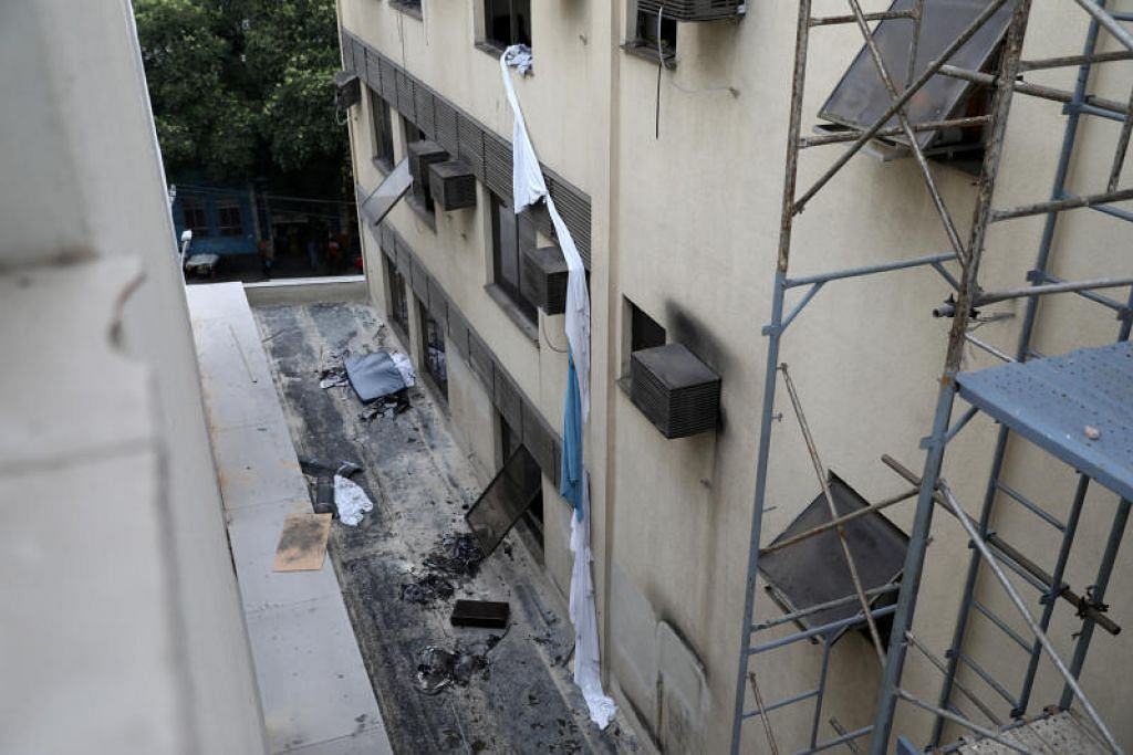 SELAMATKAN DIRI: Antara cara yang digunakan oleh pesakit dan kakitangan hospital untuk menyelematkan diri daripada api kebakaran di Hospital Badim, ialah dengan memanjat keluar tingkat hospital itu. -Foto Reuters.