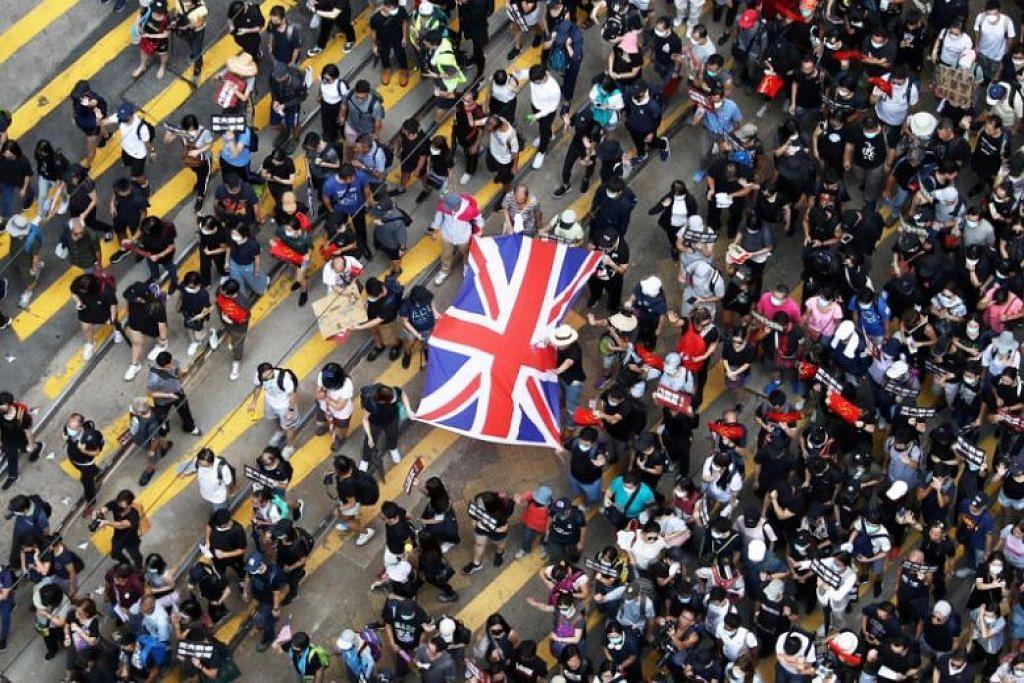 PENUNJUK PERASAAN: Selain melaungkan slogan, penunjuk perasaan turut mempamerkan bendera Amerika dan Britain (dalam gambar). -Foto Reuters.