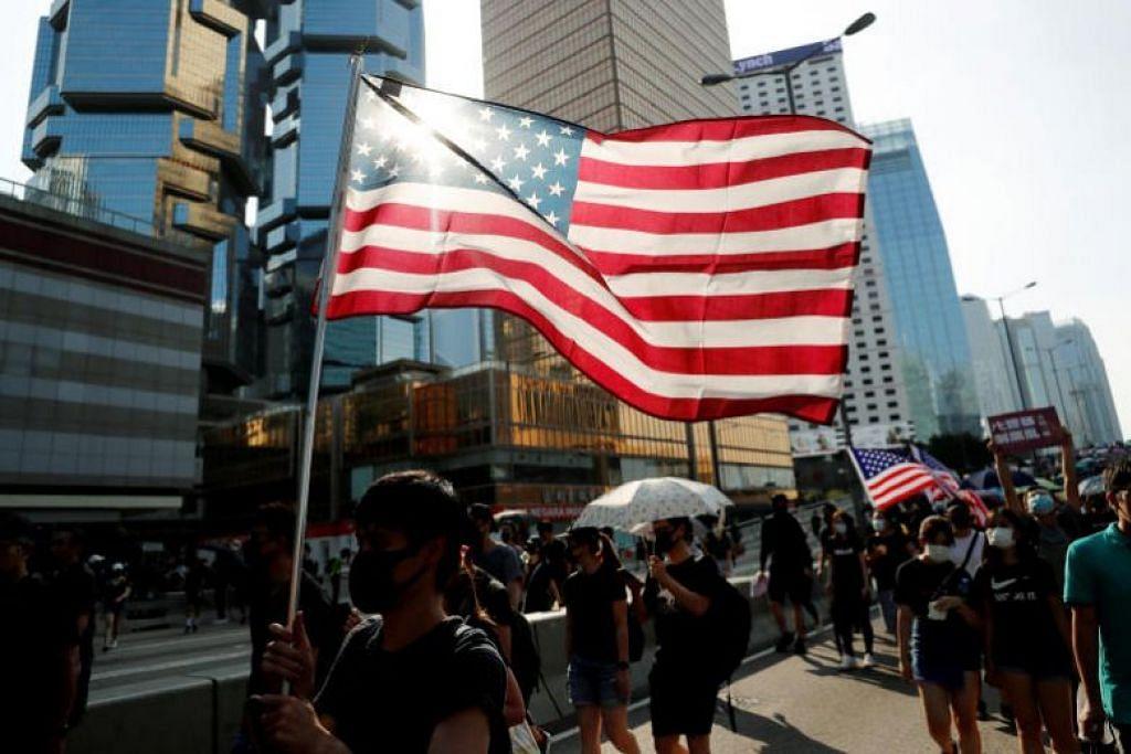 PENUNJUK PERASAAN: Selain melaungkan slogan, penunjuk perasaan turut mempamerkan bendera Amerika (dalam gambar) dan Britain. -Foto Reuters.