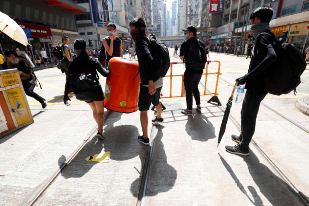 MENGHALANG TRAFIK: Penunjuk perasaan memasang benteng yang menjejas pergerakan lalu lintas di kawasan membeli-belah di Hong Kong pada Ahad. -Foto Reuters.