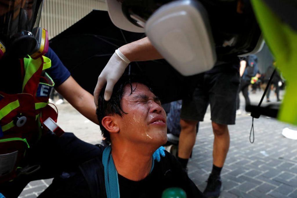 GAS PEMEDIH MATA: Polis Hong Kong telah melepaskan tembakan gas pemedih mata untuk membubarkan penunjuk perasaan. (Dalam gambar) Seorang penunjuk perasaan dibantu pegawai kecemasan untuk membasuh matanya yang terjejas akibat tembakan gas tersebut. -Foto Reuters.