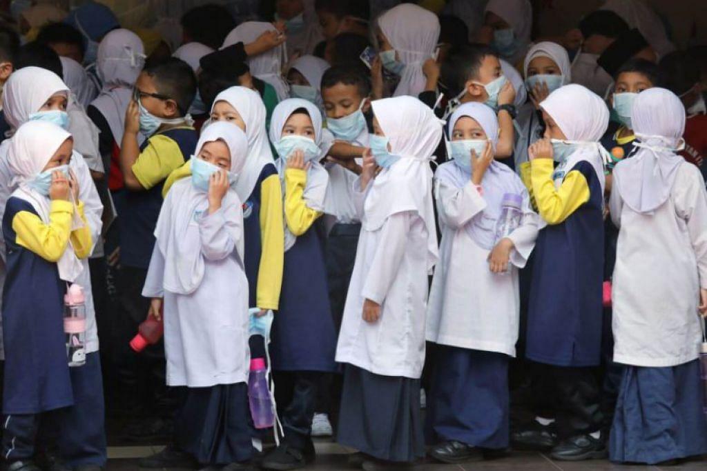 Pelajar sekolah guna pelitup apabika KL dilanda Jerebu. -Foto: REUTERS