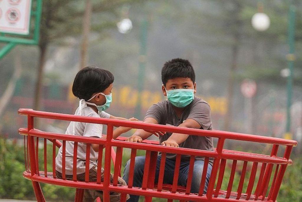 BERJEREBU: Dua kanak-kanak memakai topeng muka ketika bermain di taman permainan di Pekanbaru, Riau. Ekoran keadaan berjerebu yang mencecah tahap tidak sihat, pemerintah Riau telah menggantung kegiatan di sekolah buat sementara waktu. -Foto EPA-EFE.