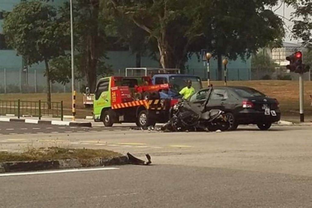 Gambar setelah kemalangan ini menunjukkan motosikal yang terbaring di jalan raya dan kereta hitam di mana pintu tepinya remuk. - Foto SINGAPORE ROADS ACCIDENTS.COM/FACEBOOK