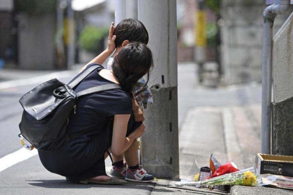PENDERAAN KEJAM: Seorang ibu dan anaknya memperingati Yua Funato, 5 tahun, yang meninggal dunia selepas lama menderita akibat didera ayah kandungnya sendiri. Foto Reuters.