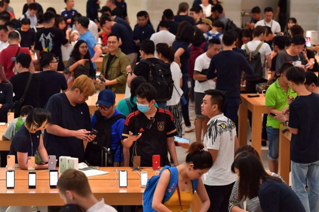 SIRI TERBARU: Orang ramai membelek-belek telefon bimbit siri terbaru Apple, iPhone 11, di cawangan utama Apple di Orchard Road, pada pagi Jumaat. -Foto BH oleh NG SOR LUAN.
