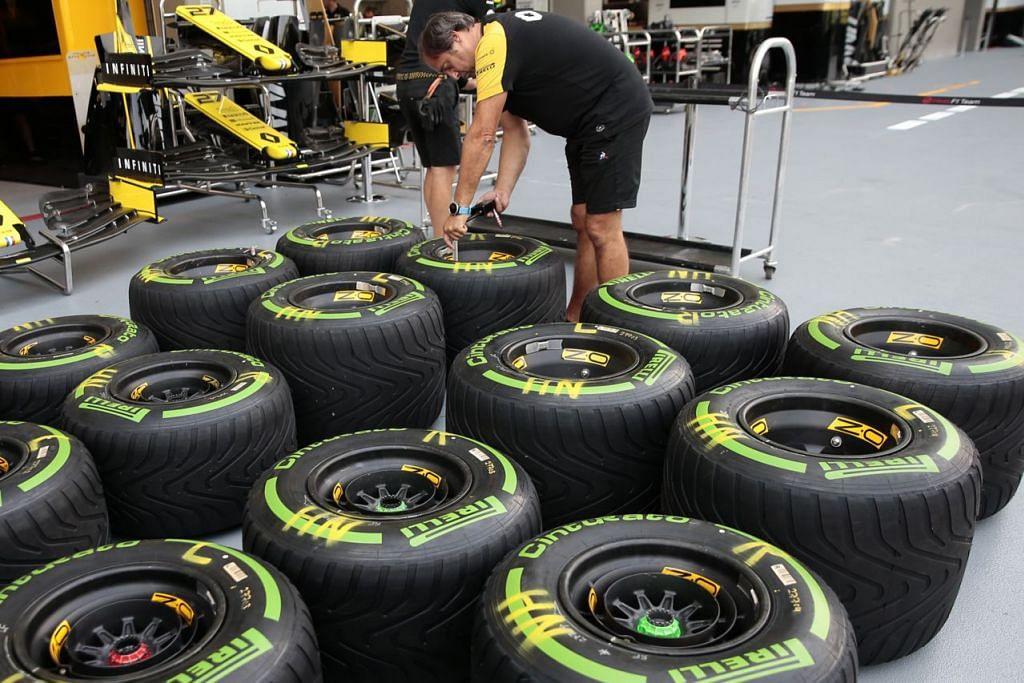 PASTIKAN SEMUA SEMPURNA: Seorang mekanik dari Team Renault Sport F1 memeriksa tayar-tayar sebelum perlumbaan. - Foto EPA-EFE