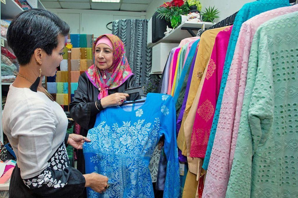 PELBAGAIKAN NIAGA: Cik Maimunah (kanan) lebih menumpukan perhatian menerima tempahan menjahit di samping menjual pakaian yang sudah siap di butiknya. – Foto BM oleh ZALEHA ABDUL KADER