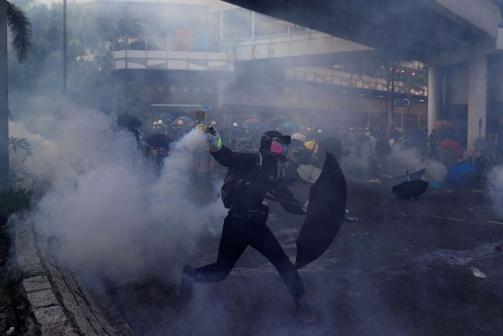 BANTAHAN DITERUSKAN: Seorang penunjuk perasaan melempar kanister gas pemedih mata semasa bantahan di daerah Sha Tin, Hongkong, semalam. – Foto REUTERS