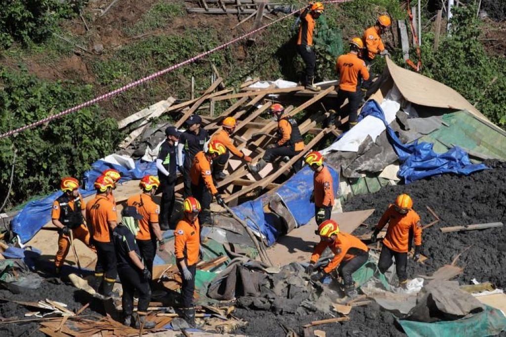 Pegawai bomba Korea Selatan mencari mangsa yang hilang di kawasan yang dilanda tanah runtuh di Busan, Korea Selatan. - Foto EPA-EFE