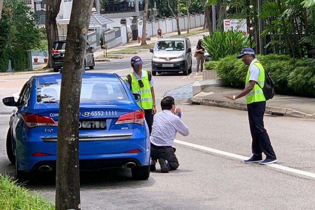 MINTA BELAS KASIHAN: Pemandu teksi ComfortDelgro yang didenda kerana merokok dalam teksinya melutut kepada pegawai Certis Cisco yang menyamannya pada Khamis (3 Oktober) di Mount Elizabeth Road. -Foto STOMP.