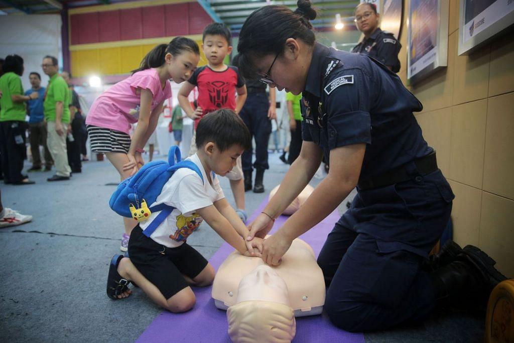 BELAJAR KEMAHIRAN BARU: Kadet CDCC Sharlyn Wee, 15 tahun, sedang mengajar Kobe Phua, empat tahun, bagaimana untuk melakukan CPR semasa pameran SGSecure di Ang Mo Kio Sabtu lalu. Perdana Menteri Lee Hsien Loong dan penasihat kepada GRC Ang Mo Kio merupakan tetamu terhormat bagi acara itu. - Foto BH oleh JASON QUAH