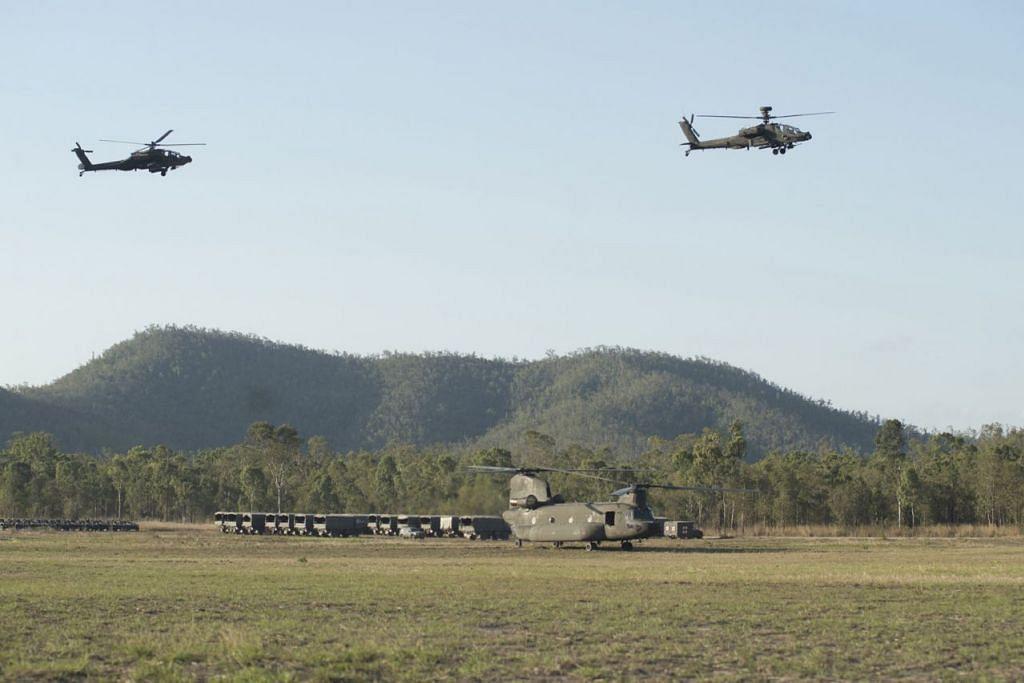 BERI PERLINDUNGAN: Dua helikopter Apache melindungi helikopter Chinook ketika sesi simulasi menghantar pasukan angkatan darat. - Foto BH oleh HARITH MUSTAFFA
