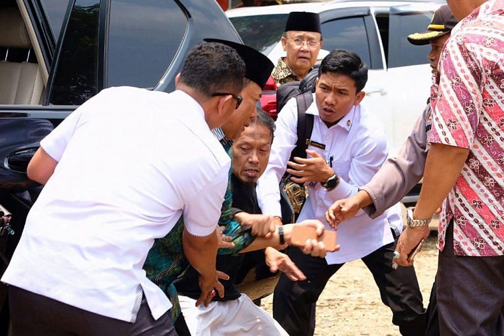 TAKTIK SERANGAN: Encik Wiranto (dua dari kiri) ditikam menggunakan 'kunai' iaitu sejenis pisau Jepun. Tikaman pada perut itu dilakukan oleh Syahril Alamsyah alias Abu Rara (tiga dari kiri), 51 tahun, yang bersekutu dengan rangkaian pro-ISIS terbesar di Indonesia, Jamaah Ansharud Daulah (JAD). - Foto EPA-EFE