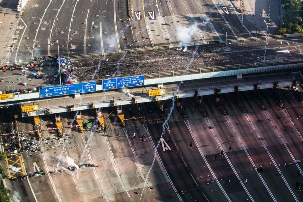 LARIKAN DIRI: Polis melepaskan gas pemedih mata ketika penunjuk perasaan berlari di jalan raya menuju ke Terowong Cross-Harbour sedang mereka cuba meninggalkan Universiti Politeknik Hong Kong semalam. – Foto-foto AFP